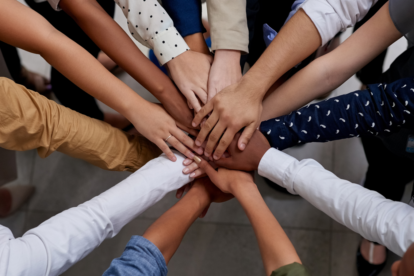 Diverse people putting hands in to signify teamwork